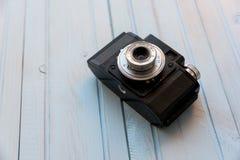 Vista superior de la cámara retra del estilo en la tabla de madera azul Imagen de archivo