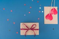 Vista superior de la caja de regalo, del confeti en forma de corazón y del sobre en azul Imagen de archivo