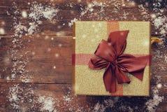 Vista superior de la caja de regalo sobre la tabla de madera nevosa Imagen de archivo