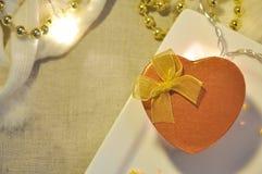 Vista superior de la caja de oro del presente del corazón con la iluminación Foto de archivo