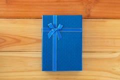 Vista superior de la caja de regalo azul con el arco de la cinta en la tabla de madera con c Foto de archivo
