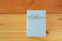 Vista superior de la caja de regalo blanca con el arco de la cinta en la tabla de madera con Imagenes de archivo