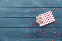 Vista superior de la caja de regalo con y de las decoraciones rojas de los corazones el día de tarjetas del día de San Valentín Imagen de archivo libre de regalías
