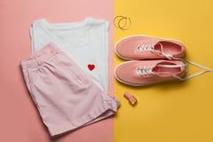 Vista superior de la camiseta de la mujer blanca y de zapatos rosados en fondo rosado y amarillo Ropa y accesorios de la moda fij fotos de archivo libres de regalías