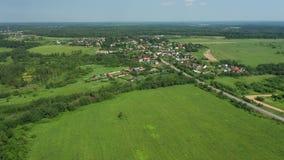 Vista superior de la carretera a través del campo y del pueblo almacen de video