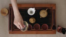Vista superior de la ceremonia de té que ocurre en una pequeña tabla de madera Las manos de la muchacha que vierten té en pequeña almacen de video
