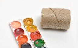 Vista superior de la composición con las pinturas de la acuarela y la guita usadas del filamento en las bobinas aisladas en un fo Imagen de archivo libre de regalías