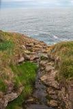Vista superior de la corriente entre las rocas que flujos en el mar fotografía de archivo libre de regalías