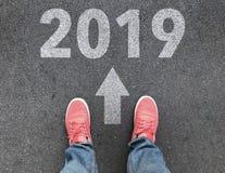 Vista superior de la flecha del pie, blanca y 2019 del texto en la carretera de asfalto, concepto del Año Nuevo del comienzo imagen de archivo