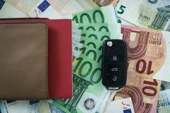 Vista superior de la llave del coche en una pila de billetes de banco euro como financi del coche Fotografía de archivo