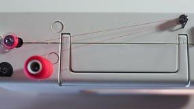 Vista superior de la máquina de coser Rebobina los hilos del carrete a la bobina La cámara resbala hacia la izquierda metrajes