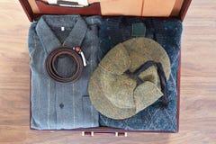 Vista superior de la maleta vieja con ropa en piso de madera imágenes de archivo libres de regalías