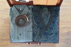Vista superior de la maleta vieja con ropa en piso de madera Imagen de archivo