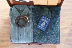 Vista superior de la maleta vieja con ropa y del pasaporte en flo de madera imagen de archivo