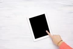 Vista superior de la mano de una mujer que señala a una tableta Fotos de archivo