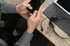 vista superior de la mano del hombre usando las auriculares de VOIP con los comp digitales de la tableta Foto de archivo libre de regalías