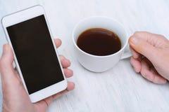Vista superior de la mano del viejo hombre que sostiene una taza de café y de smartphone Foto de archivo