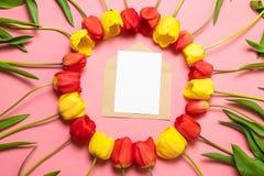 Vista superior de la maqueta minimalistic de la tarjeta con los tulipanes rojos en un fondo rojo Endecha plana con el espacio de  imágenes de archivo libres de regalías