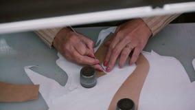Vista superior de la materia textil del dublerine del corte de la mano de la mujer s en el lugar de trabajo de la fábrica Diseñad metrajes