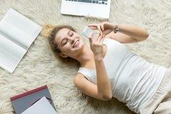 Vista superior de la mensajería de la mujer joven en el teléfono en casa Imagenes de archivo