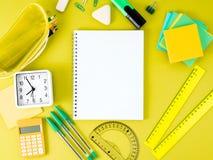 Vista superior de la mesa amarilla de la oficina con el cuaderno en la jaula, escuela Fotografía de archivo