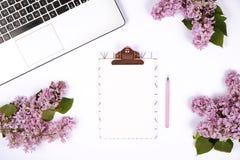 Vista superior de la mesa del trabajador de sexo femenino con el ordenador portátil, las flores y diversos artículos de los mater Fotografía de archivo
