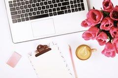 Vista superior de la mesa del trabajador de sexo femenino con el ordenador portátil, las flores y diversos artículos de los mater imagen de archivo