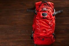 Vista superior de la mochila anaranjada brillante del viaje en un fondo de madera Fotos de archivo