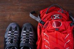 Vista superior de la mochila turística y de los zapatos juguetones en los tableros de madera imagen de archivo