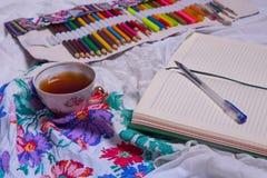 Vista superior de la pintura, una hoja de papel en blanco, taza de té, marcadores Imagenes de archivo