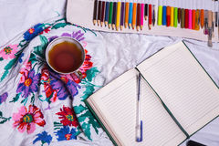 Vista superior de la pintura, una hoja de papel en blanco, taza de té, marcadores Fotografía de archivo