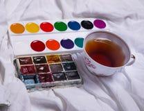 Vista superior de la pintura, una hoja de papel en blanco, taza de té, marcadores Foto de archivo