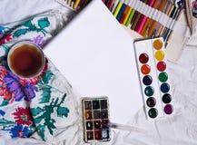 Vista superior de la pintura, una hoja de papel en blanco, taza de té, marcadores Imágenes de archivo libres de regalías