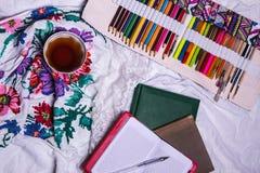Vista superior de la pintura, una hoja de papel en blanco, taza de té, marcadores Foto de archivo libre de regalías
