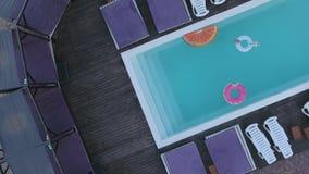 Vista superior de la piscina con los círculos inflables coloreados brillantes Tiroteo del abejón almacen de video