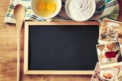 Vista superior de la pizarra y de la cuchara de madera sobre la tabla y el collage de madera de fotos con la diversos comida y pl Fotos de archivo