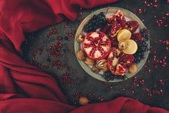 Vista superior de la placa con las granadas, las uvas y los limones Fotografía de archivo libre de regalías