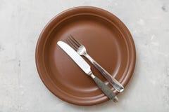 Vista superior de la placa marrón con platos y cubiertos en el hormigón Imagen de archivo libre de regalías