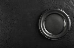 Vista superior de la placa vacía negra en fondo de piedra negro imagenes de archivo