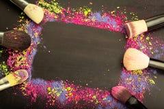 Vista superior de la plantilla colorida del marco del maquillaje con los cepillos del maquillaje Fotografía de archivo