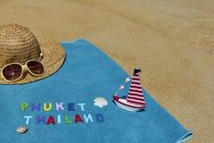 Vista superior de la playa arenosa con los accesorios del verano con las palabras de PHUKET TAILANDIA Imagen de archivo libre de regalías