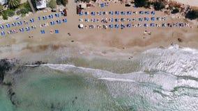 Vista superior de la playa arenosa en las orillas del mar cristalino equipadas de los ociosos del sol, Coral Bay, Chipre almacen de metraje de vídeo