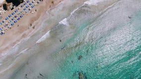 Vista superior de la playa arenosa en orillas del mar cristalino con los ociosos y las huéspedes del sol almacen de video