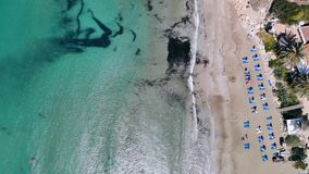 Vista superior de la playa arenosa en orillas del mar cristalino con los ociosos y las hu?spedes del sol metrajes
