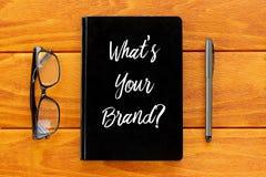 Vista superior de la pluma, de lentes, y del libro escrito con la pregunta What' ¿s su marca? en fondo de madera Concepto de fotografía de archivo libre de regalías