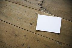 Vista superior de la postal o del documento blanca sobre viejo fondo de madera imagen de archivo