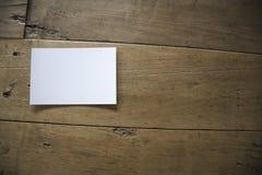 Vista superior de la postal o del documento blanca sobre viejo fondo de madera foto de archivo