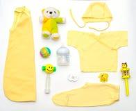 Vista superior de la ropa del amarillo del bebé y de la materia del juguete Fotos de archivo libres de regalías