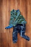 Vista superior de la ropa del ` s de los niños y del coche azul del juguete en fondo de madera Fotografía de archivo
