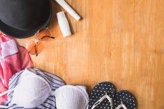 Vista superior de la ropa y de los accesorios del verano para la mujer en la tabla de madera Concepto de las vacaciones Fotos de archivo libres de regalías